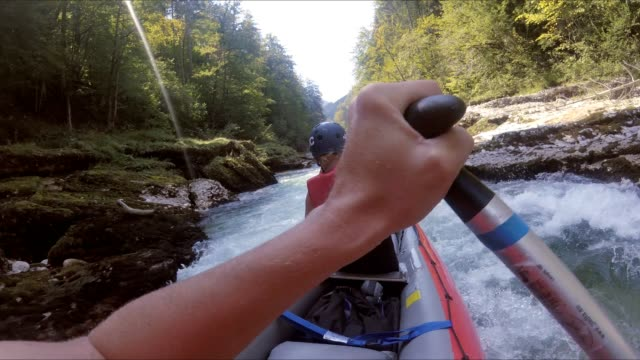 Girl paddling wild rapids in inflatable kayak on Salza river Austria