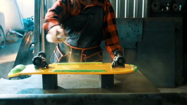 girl painting a skateboard - sprzęt sportowy filmów i materiałów b-roll