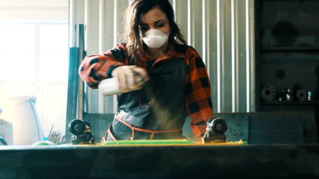 vídeos de stock e filmes b-roll de girl painting a skateboard - bricolage