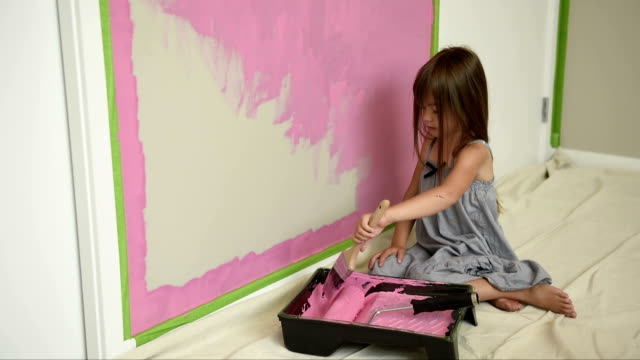 Girl painting her bedroom pink