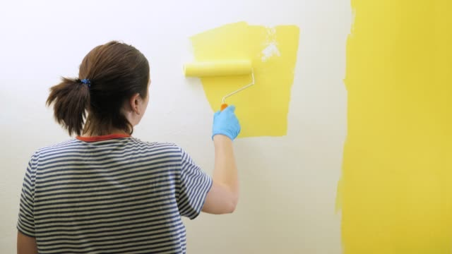 girl paints wall with roller in her right hand in yellow. she is wearing striped shirt and blue gloves. slow motion view and medium shot - taca filmów i materiałów b-roll