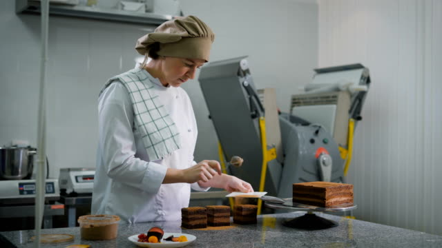 Girl pastry chef dressed in white suit and a brown cap, with a serious look sprinkles, chocolate cakes, which are standing on the table, cocoa powder video