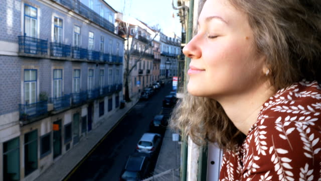 girl peeps out of hotel window looking at tourist city - vídeo