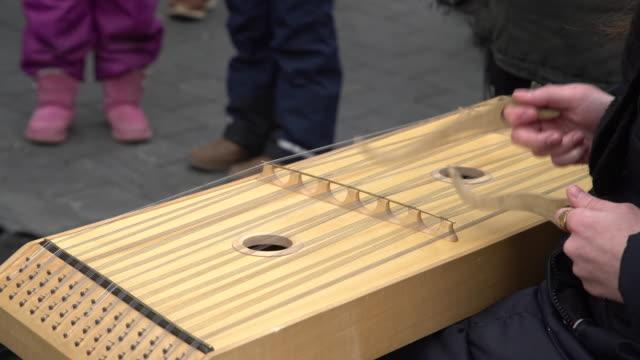 ragazza che esegue musica con strumento a corda tradizionale alla tariffa per strada - fare video stock e b–roll