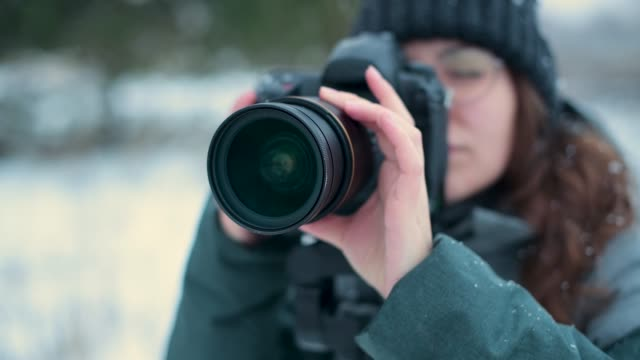 girl photographer takes a picture of landscape outdoors on a winter day