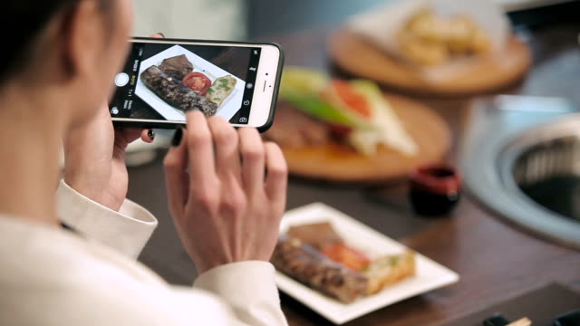 Girl photographing food in a restaurant video