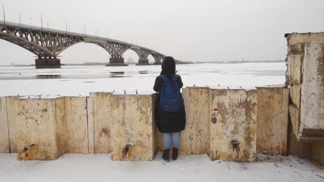 A girl photographs in the street by the river in winter. Woman photographer takes pictures by the bridge in the city.