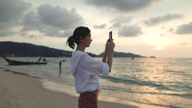 Girl photographs the sunset sky on the beach.