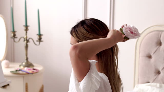 Girl pinning her long hair with a hairpin in the form of a peony flower.