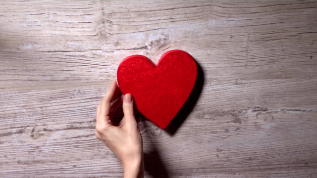 Girl placing red heart on a wooden table, top view. Romance, love, Valentine's day, solitude concepts. FullHD video video