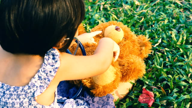 girl playing doctor with bear in the garden - purezza video stock e b–roll