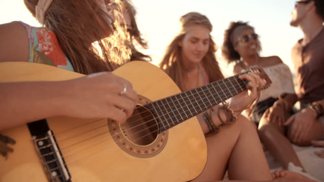stockvideo's en b-roll-footage met girl playing her guitar on the beach with friends - boho