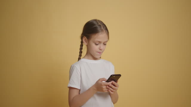 Girl playing in her cell phone at yellow wall background slow motion