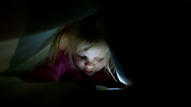 Girl playing on cell phone under duvet video