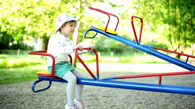 Girl playing on seesaw. video