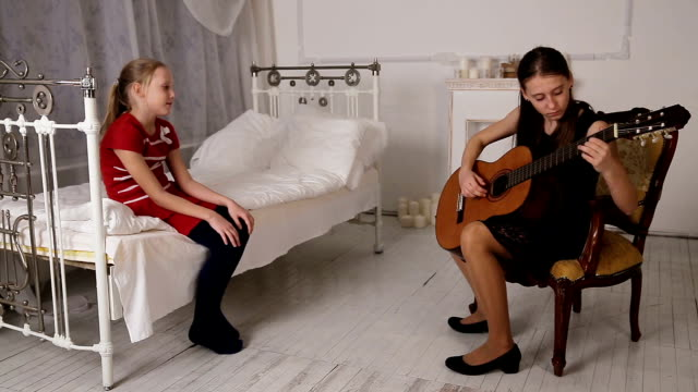 Girl playing the guitar Young girl in black dress playing guitar sitting in front of a child and listening to how to play guitar .Young girl playing music on acoustic guitar.Young girl looks like her sister plays the guitar rocking chair stock videos & royalty-free footage
