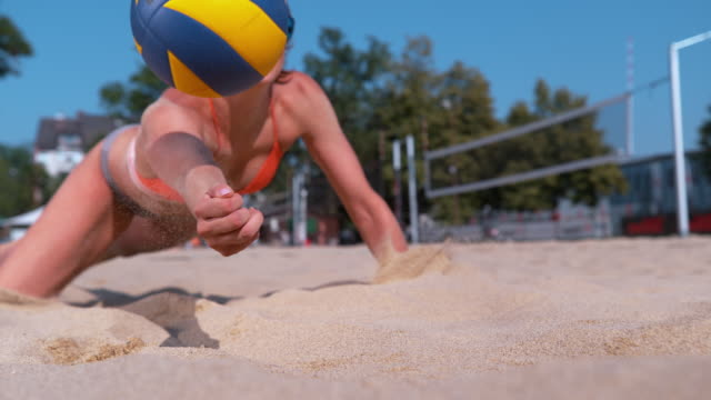 SLOW MOTION: Girl playing volleyball jumps into sand and strikes ball with hand. SLOW MOTION, CLOSE UP, DOF: Athletic Caucasian girl playing beach volleyball jumps into the sand and strikes the ball with her hand. Cinematic shot of fit female volleyball player saving a point. beach volleyball stock videos & royalty-free footage