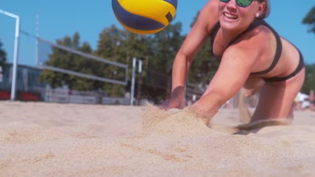 SLOW MOTION: Girl playing volleyball jumps to strike the ball with one hand. SLOW MOTION, CLOSE UP, DOF: Athletic Caucasian girl playing volleyball jumps to strike the ball with one hand. Young female athlete dives into the sand and saves a point during beach volleyball match. diving to the ground stock videos & royalty-free footage