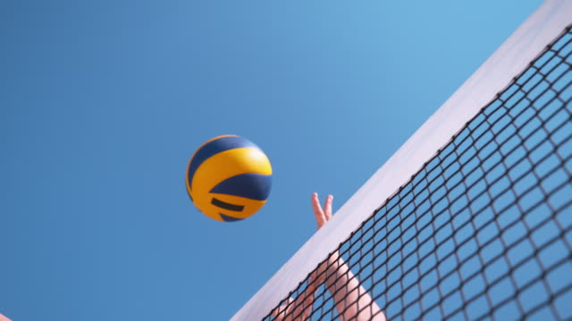 SLOW MOTION: Girl playing volleyball spikes the ball and opponent blocks it. SLOW MOTION, CLOSE UP, LOW ANGLE: Unrecognizable girl playing volleyball spikes the ball and opponent blocks it at the net. Unknown person's hands striking the ball during a beach volleyball game. beach volleyball stock videos & royalty-free footage
