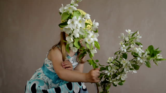 Girl playing with a blooming apple twig video