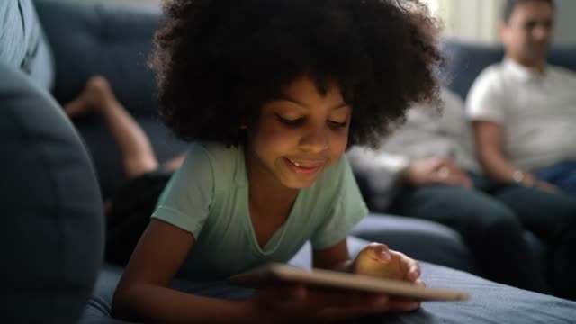 Girl playing with digital tablet at home