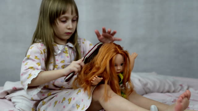 Girl playing with doll sitting on the bed video