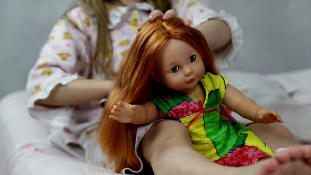 Girl playing with doll sitting on the bed Girl playing with doll sitting on the bed, she braids her hair doll stock videos & royalty-free footage
