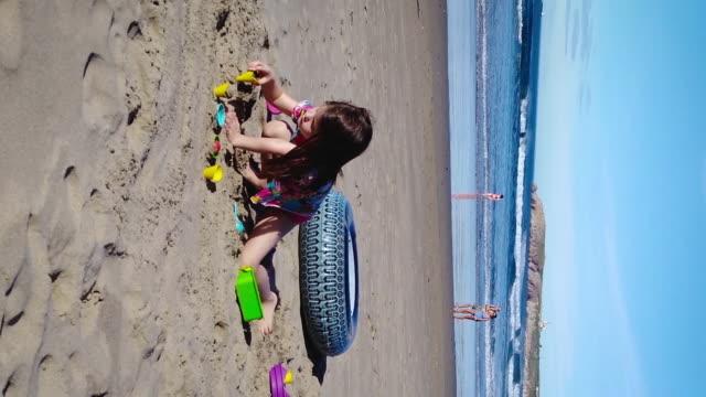 flicka som leker med hennes leksaker på stranden - vertikal bildbanksvideor och videomaterial från bakom kulisserna