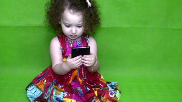 Girl playing with phone. Green Background. video