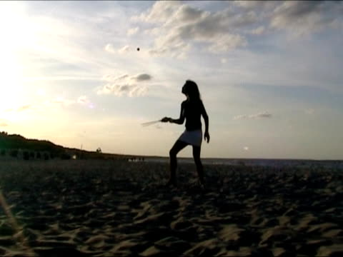 Girl playing with racket at the beach video