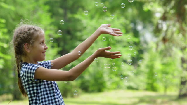 Girl playing with soap bubbles outdoor. Slow motion.