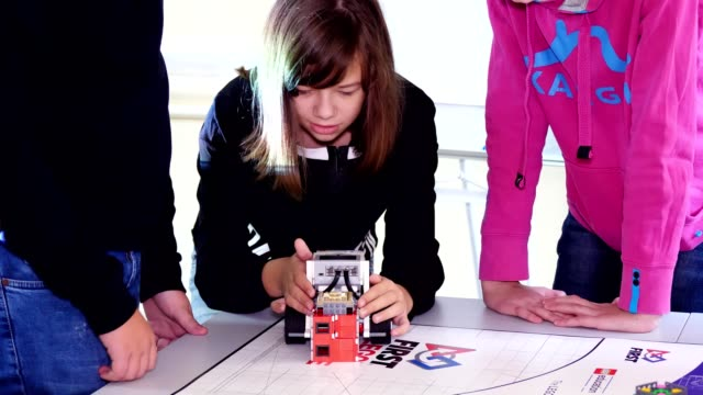 girl plays with a robot, machine, made of small designer details. machine moves, can perform certain actions. educational lesson at school of Robotics, STEM education - vídeo