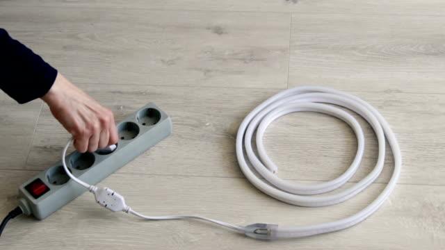 vidéos et rushes de la fille branche le protecteur électrique de surtension et allume la lumière. concept d'une nouvelle idée. - vidéos de rallonge électrique