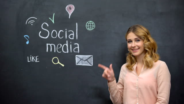 Girl pointing at social media signs on blackboard, addiction to networking