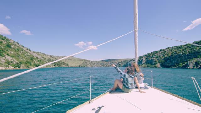 彼女の母親と一緒にヨットに座ってどこかを指して ws 女の子 - デッキ点の映像素材/bロール