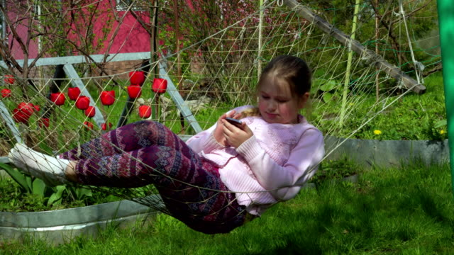4K Girl Portrait Playing Tablet in Hammock, Child Face Use Smart Phone in Nature video
