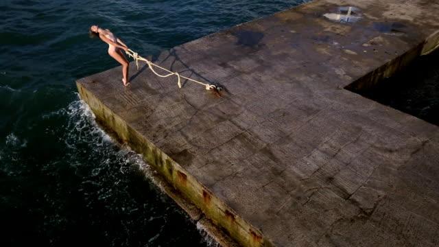 vidéos et rushes de femme qui pose sur le front de mer - justaucorps
