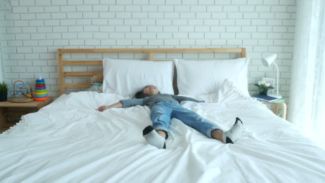 vídeos y material grabado en eventos de stock de chica posando juego nieve en cama - colchón
