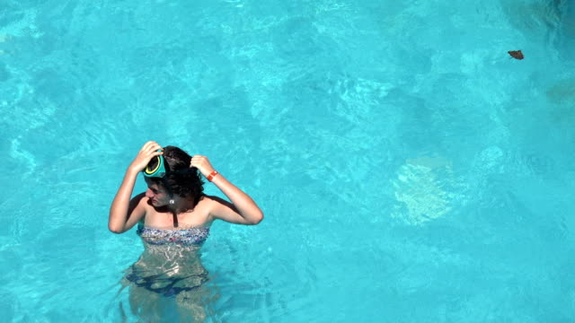 Girl preparation for diving, putting on snorkeling mask Girl preparation for diving, putting on snorkeling mask aqualung diving equipment stock videos & royalty-free footage