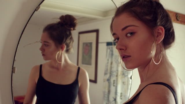 Girl prepares to go out in front of the mirror