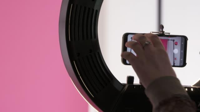 vídeos de stock, filmes e b-roll de parar iniciar botão para gravar a empurrar na tela do telefone e falar com a câmera - blogar