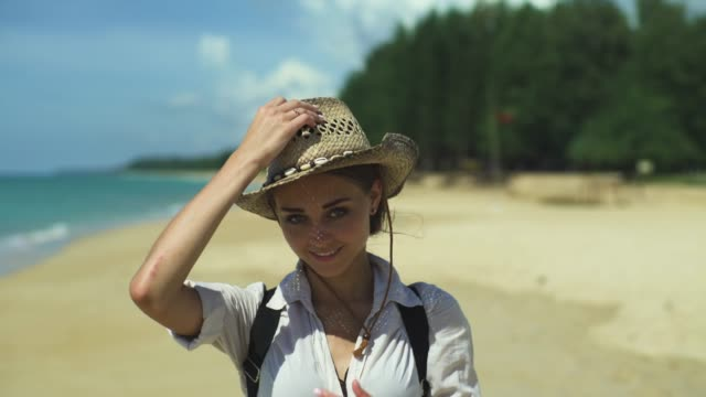 Girl Puts A Hat On His Head On The Beach video