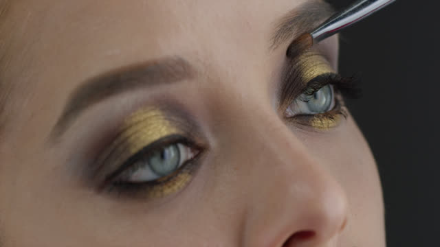 girl puts eye shadow. fashion video. make-up. 4k 30fps prores 4444 stock video - театральный грим стоковые видео и кадры b-roll