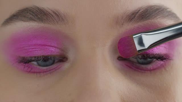 vidéos et rushes de la fille met l'ombre d'oeil. vidéo de mode. maquillage. - fard à paupières