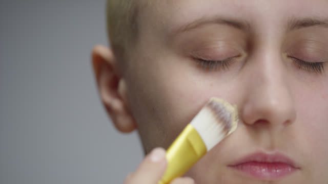 vídeos de stock e filmes b-roll de girl puts foundation on her face. fashion video. make-up. 4k 30fps prores 4444 - sombra para os olhos