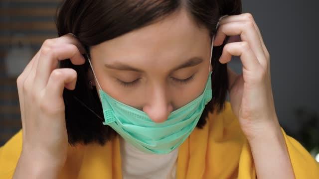 女の子は呼吸マスクを着用します。魅力的な女性はフェイスマスクを着用し、カメラを見ます。風邪、インフルエンザ、ウイルス、扁桃炎、急性呼吸器疾患、検疫、流行の概念。スローモー� - 着る点の映像素材/bロール