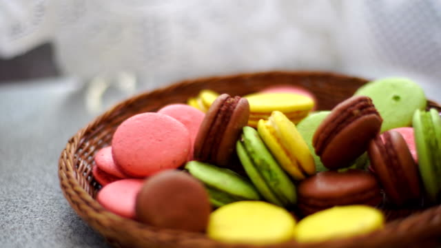 girl puts the wicker plate with macaroon biscuits on the table video
