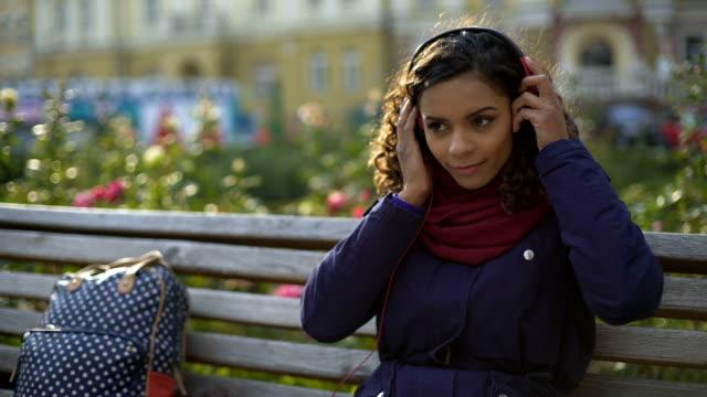 Girl putting on earphones, enjoying atmosphere of favorite band concert video