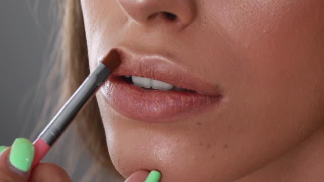 stockvideo's en b-roll-footage met meisje dat lipgloss met een kleine borstel zet - make up