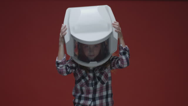 vídeos de stock e filmes b-roll de girl putting on oversized helmet - vr red background